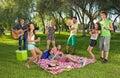 Happy teenage friends enjoying a picnic outdoors