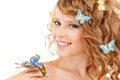 Happy teenage girl with butterflies in hair health and beauty concept and one sitting on her hand Stock Images