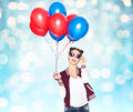 Happy teenage girl with helium balloons people teens holidays party and summer concept smiling pretty in sunglasses over blue Royalty Free Stock Photos