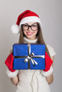 Happy teenage girl holding a blue gift box cute caucasian with santa hat wearing gloves and nerd glasses christmas and giving Royalty Free Stock Photos