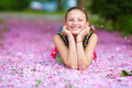 Happy teenage girl lying in pink petals spring garden smiling Stock Photo