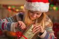 Happy teenage girl in santa hat opening christmas present box Royalty Free Stock Photo