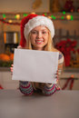 Happy teenage girl in santa hat showing blank paper sheet christmas decorated kitchen Stock Images