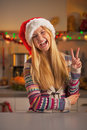Happy teenage girl in santa hat showing victory gesture christmas decorated kitchen Royalty Free Stock Images