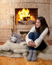 Happy teenage girl sitting fireside Royalty Free Stock Photo