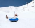Happy teenage girl sliding down on snow tube