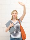Happy teenage girl waving a greeting with laptop Stock Photography
