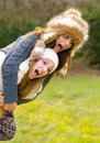 Happy teenage girls piggyback riding in the nature on beautiful autumn day Royalty Free Stock Images