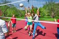 Happy teenage kids play volleyball outside Royalty Free Stock Photo