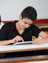 Happy teenage schoolboy using tablet at desk digital in classroom Royalty Free Stock Images