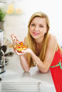 Happy teenager girl eating fresh fruits salad in kitchen modern Royalty Free Stock Images