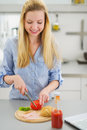 Happy teenager girl making sandwich in kitchen on table Stock Photos