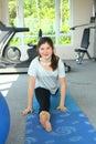 Happy teenager girl on mat in gym make split smiling portait Royalty Free Stock Image