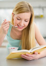 Happy teenager girl reading book and eating yogurt in kitchen Royalty Free Stock Images