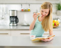 Happy teenager girl reading book and eating yogurt in kitchen Royalty Free Stock Photography