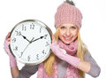 Happy teenager girl in winter hat and scarf showing clock high resolution photo Stock Photography