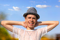 Happy teenager in a hat narrowing his eyes the bright sun Stock Image