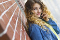 Happy teenager on a mobile phone beutiful young woman her while leaning against brick wall Stock Photography