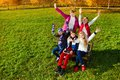 Happy teens in autumn park group of kids sitting on the bench and lifting hands boys and girls Royalty Free Stock Photos