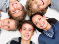 Happy teens smiling and lying on white floor Stock Image
