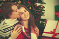 Happy tender loving couple in embrace warmed at Christmas tree Royalty Free Stock Photo