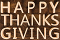Happy thanks giving the words are formed out of wooden letters set agains a wooden background Royalty Free Stock Images