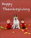 Happy thanksgiving cute white jack russell terrier dog wearing pilgrim hat is posed with two pilgrim paper children on brown Stock Image