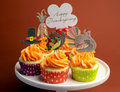 Happy thanksgiving decorated cupcakes on pink stand with message turkey pilgrim hat and corn toppers cake against a brown Royalty Free Stock Image