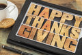Happy thanksgiving on digital tablet in letterpress wood type computer with stylus pen coffee cup and cookie Royalty Free Stock Image