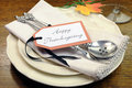 Happy thanksgiving individual dinner table place setting with best dinnerware and silverware and greeting tag Stock Photo