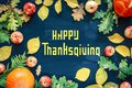 Happy Thanksgiving text with pumpkins and leaves over dark wood background Royalty Free Stock Photo