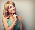 Happy thinking young woman with blond short hairstyle looking wi finger under face color toned portrait Stock Photos