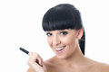 Happy thoughtful attractive young woman holding a pen with black hair and hispanic or european features looking at camera smiling Royalty Free Stock Image