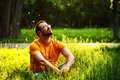 A happy thoughtful dreamer man is sitting on green grass in park Royalty Free Stock Photo