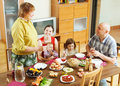 Happy three generations family around festive table together at home Royalty Free Stock Photos