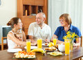 Happy three generations family eating friuts over table at home interior Royalty Free Stock Photography