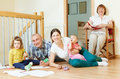 Happy three generations family enjoying in home together with two children at floor Stock Images