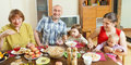 Happy three generations family posing over celebratory table Royalty Free Stock Photo
