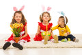 Happy three kids with bunny ears sitting in aline on carpet easter eggs Royalty Free Stock Photography
