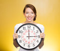 Happy time closeup portrait young smiling business woman successful executive banker employee holding wall clock isolated yellow Stock Photography