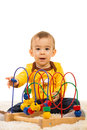 Happy toddler boy playing with wooden toy and sitting on fur carpet home Royalty Free Stock Image
