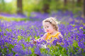 Happy toddler girl in bluebell flowers in spring forest