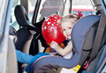 Happy toddler girl in car seat with a red balloon hand Stock Photos