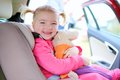 Happy toddler girl enjoying safe trip in the car portrait of little child cute blonde sitting comfortable seat with safety belts Royalty Free Stock Photo