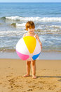 Happy toddler girl playing with her colorful ball at beach Royalty Free Stock Photography