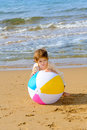 Happy toddler girl playing with her colorful ball at beach Stock Image