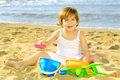 Happy toddler girl playing with her toys at beach Royalty Free Stock Image