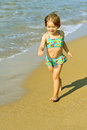 Happy toddler girl running on beach Stock Photo