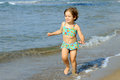 Happy toddler girl running at beach Stock Image