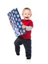 Happy toddler holding gift on white little boy laughing and running toward camera with christmas isolated Stock Image